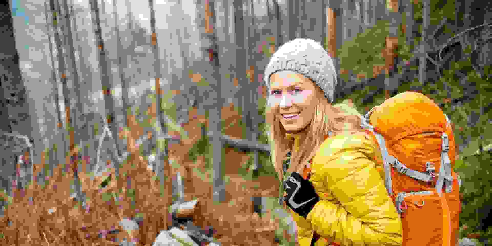 Eine Frau wandert in orange farbener Thermojacke durch den Wald. Auf dem Rücken trägt sie einen großen Wanderrucksack.