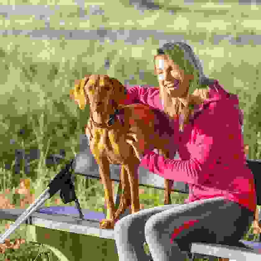 Eine blonde Frau sitzt mit einem braunen Hund auf einer Parkbank.