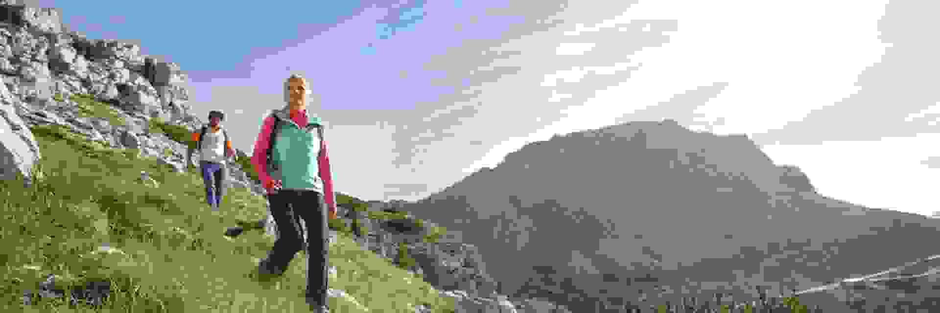 Eine Frau läuft in Wanderhosen einen Berg hinab. Im Hintergrund ist ein Mann zu sehen, der ihr folgt.