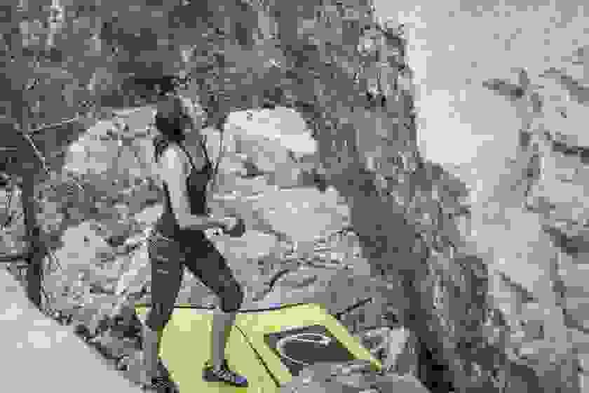 Eine Frau steht vor einer Felswand und schaut nach oben. Vor ihr liegt eine Bouldermatte für die Sicherheit.