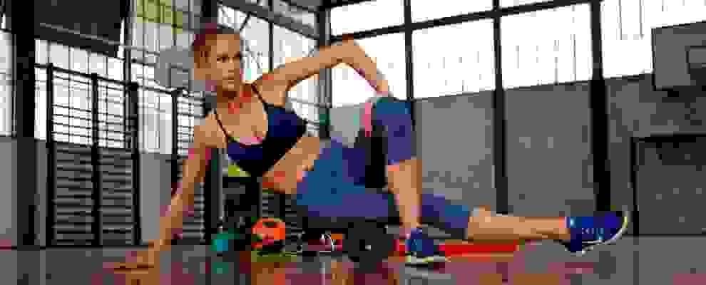 Eine Frau trainiert mit einer Faszienrolle in dunkelblauer Trainingshose und Sport-BH.