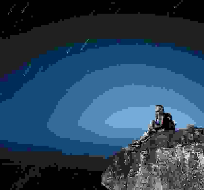 Eine Frau sitzt auf einem Berg und schaut zum Sternenhimmel hinauf.