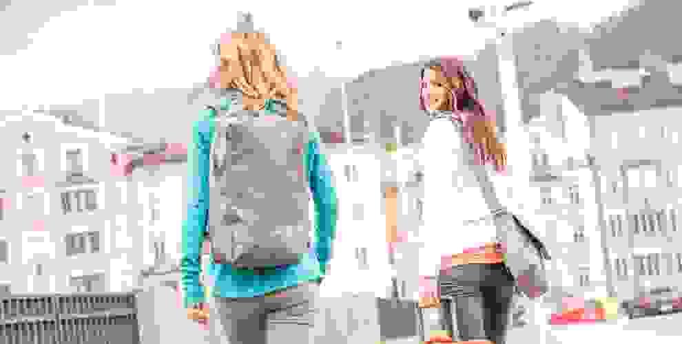 2 Frauen gehen in einer Stadt spazieren. Eine von ihnen trägt einen speziellen Rucksack für Frauen auf dem Rücken.