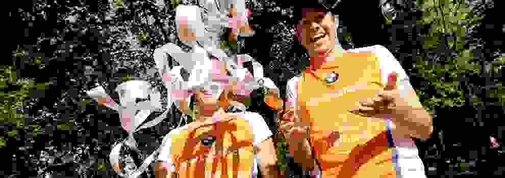 Zwei Läufer vom Stadtlauf Freiburg feiern und werfen eine Handvoll Medaillen in die Luft.