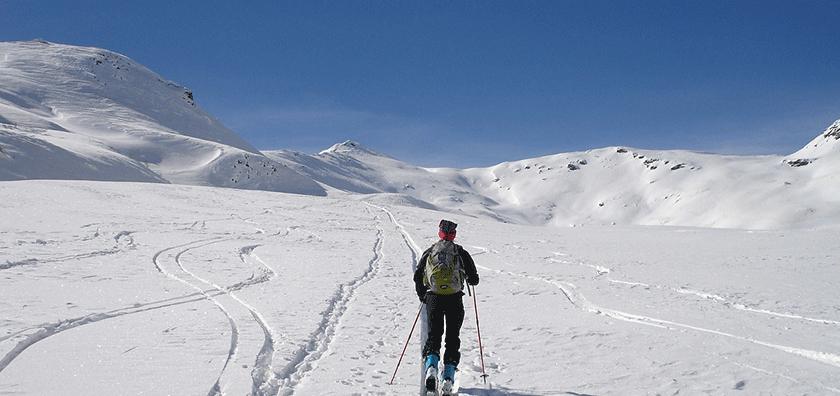 Ein Skitourenfahrer fährt in einer Schneelandschaft auf einen Berg zu.