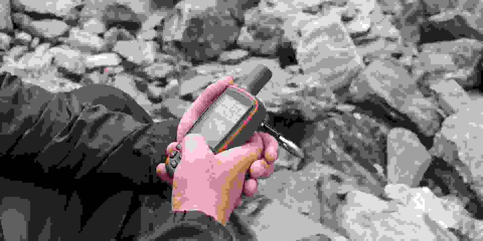 Ein GPS-Gerät dient einem mann beim Geocaching zur Orientierung.