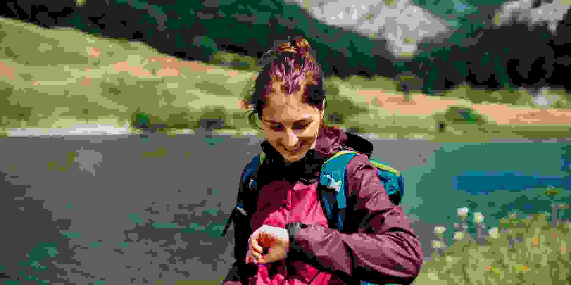 Eine Frau trägt wetterfeste Kleidung beim Geocahing während sie auf ihre GPS Uhr schaut.