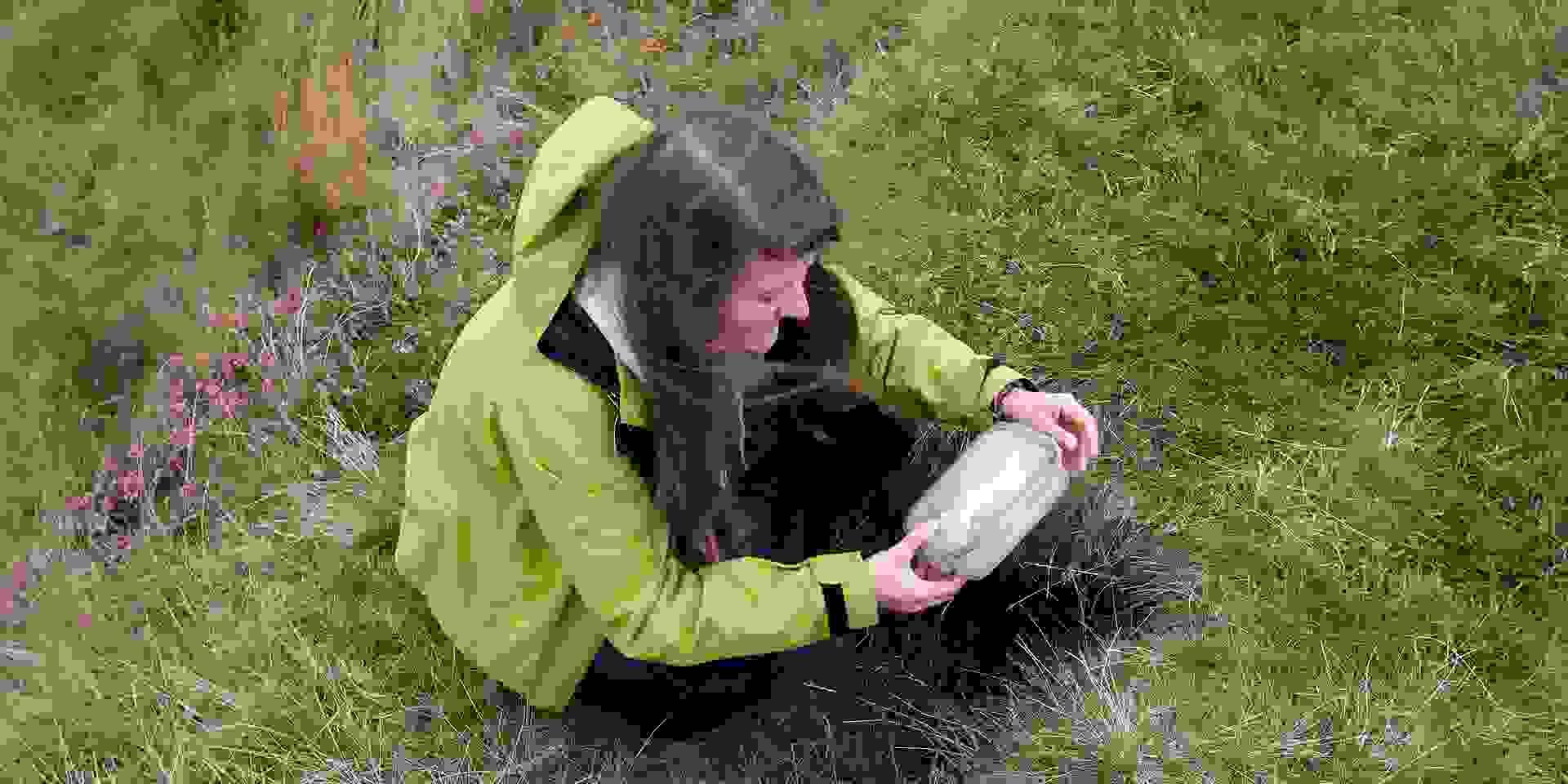 Eine junge Frau verbuddelt beim Geocaching einen Cache.