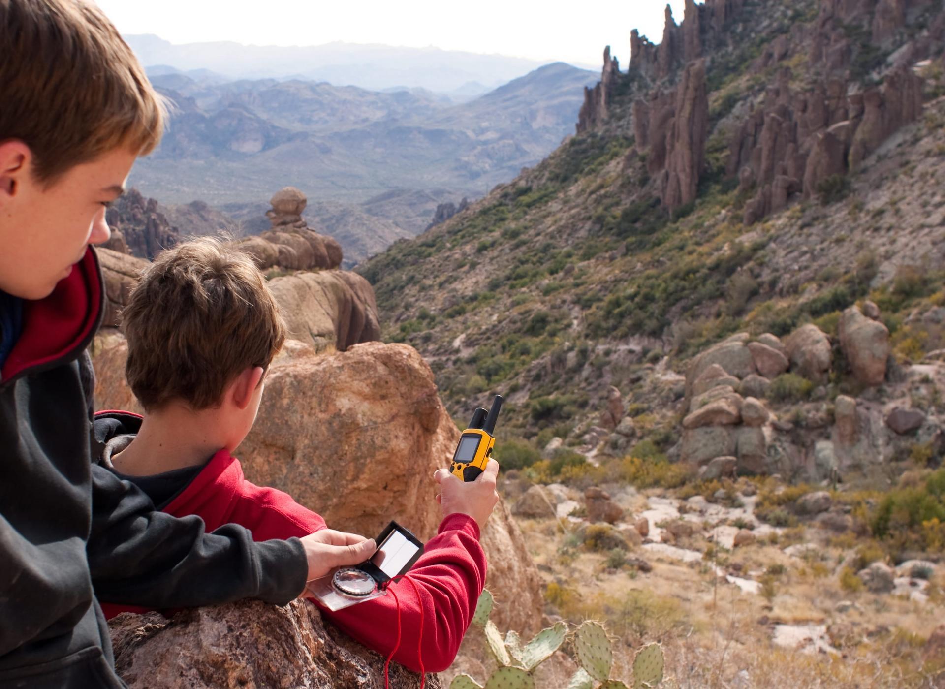 Zwei Kinder beim Geocaching mit Kompass und GPS-Gerät.