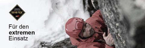 Ein Mann klettert eine Bergwand hinauf. Er trägt einen roten Schutzhelm und eine rote Gore Tex Pro Jacke.