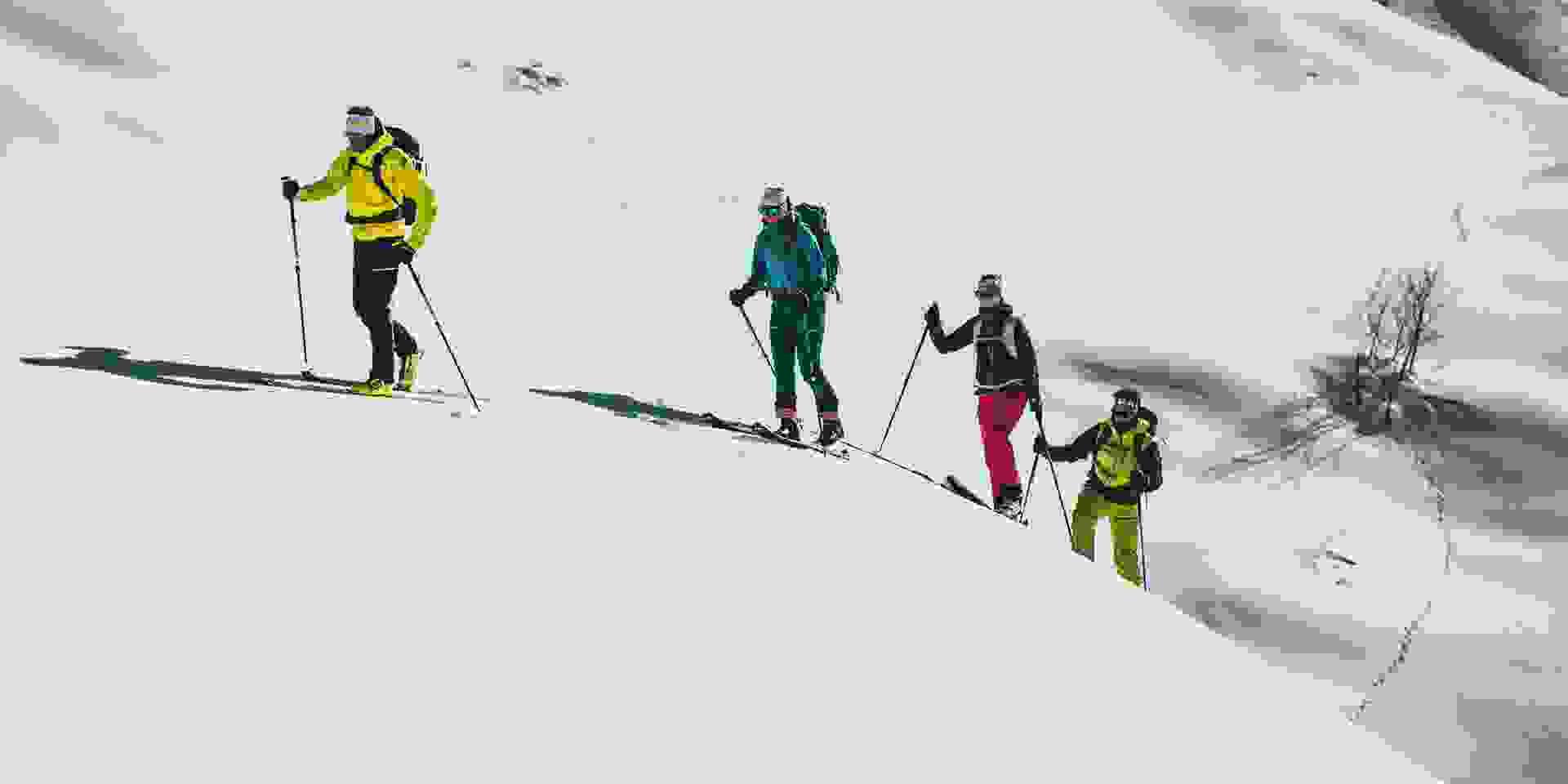 Eine Gruppe Skitourengeher erklimmen eine kleine Anhöhe