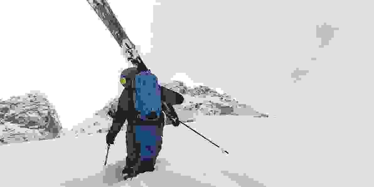 Ein Mann im hohen Pulverschnee, seine Tourenski geschultert.