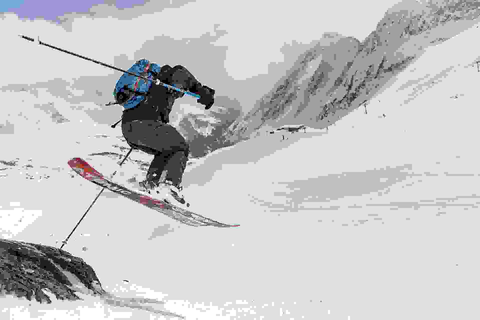Ein Freeride Skifahrer springt mit seinen Freeride Ski über einen kleinen Abgrund