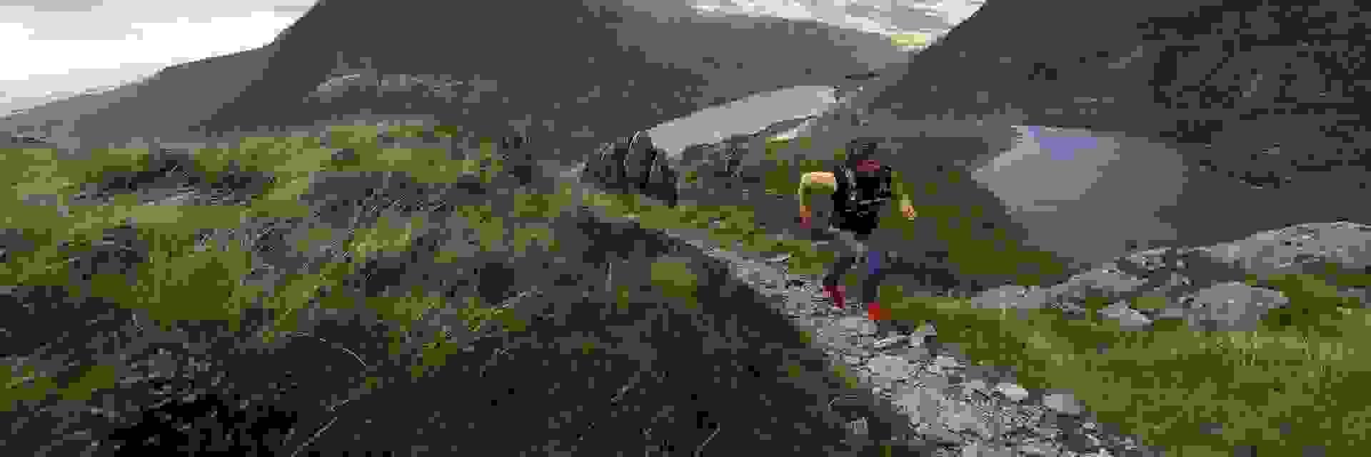 Ein Mann beim Trailrunning. Es geht auf einem steinigen Pfad steil bergauf.