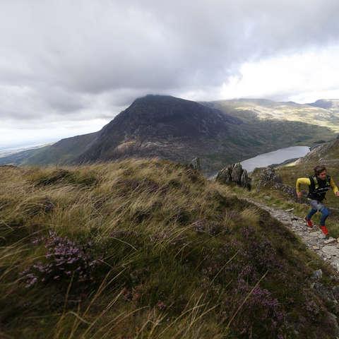 Ein Mann läuft einen anspruchsvollen Trail in den Bergen.