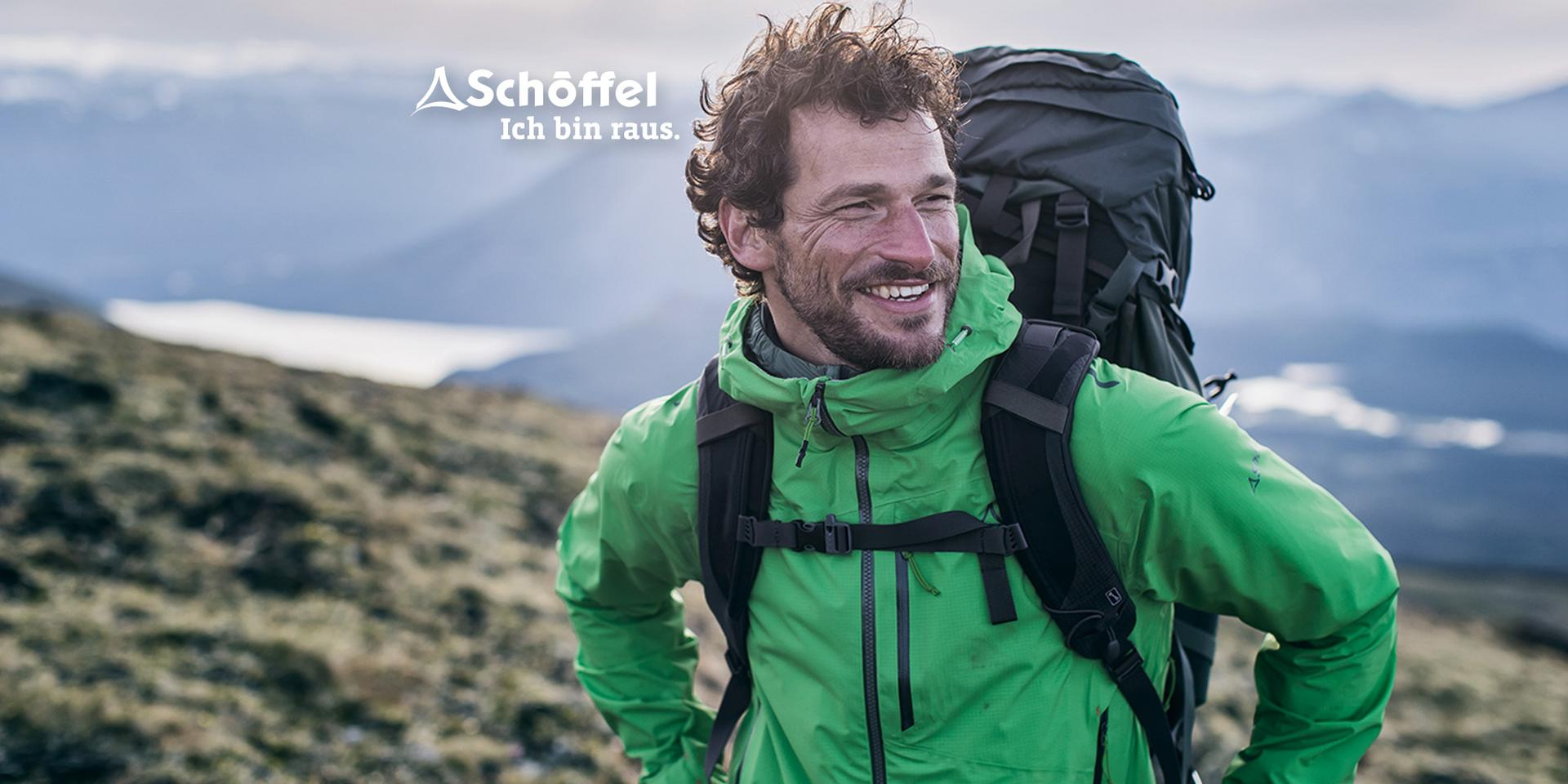 Ein Mann wandert durch eine Berglandschaft und trägt eine Schöffel Zipin Jacke.