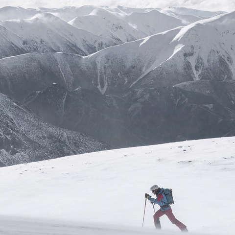 Ein Skitourengeher der entlang einer Gebirgskette wandert.