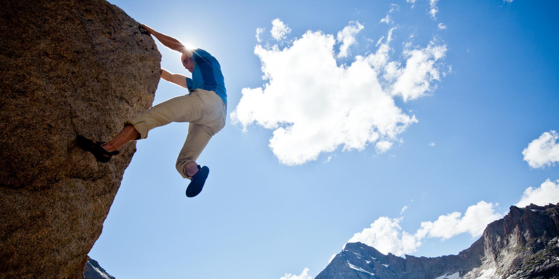Ein Boulderer klettert ein Boulderproblem hinauf und im Hintergrund ist ein Bergpanorama