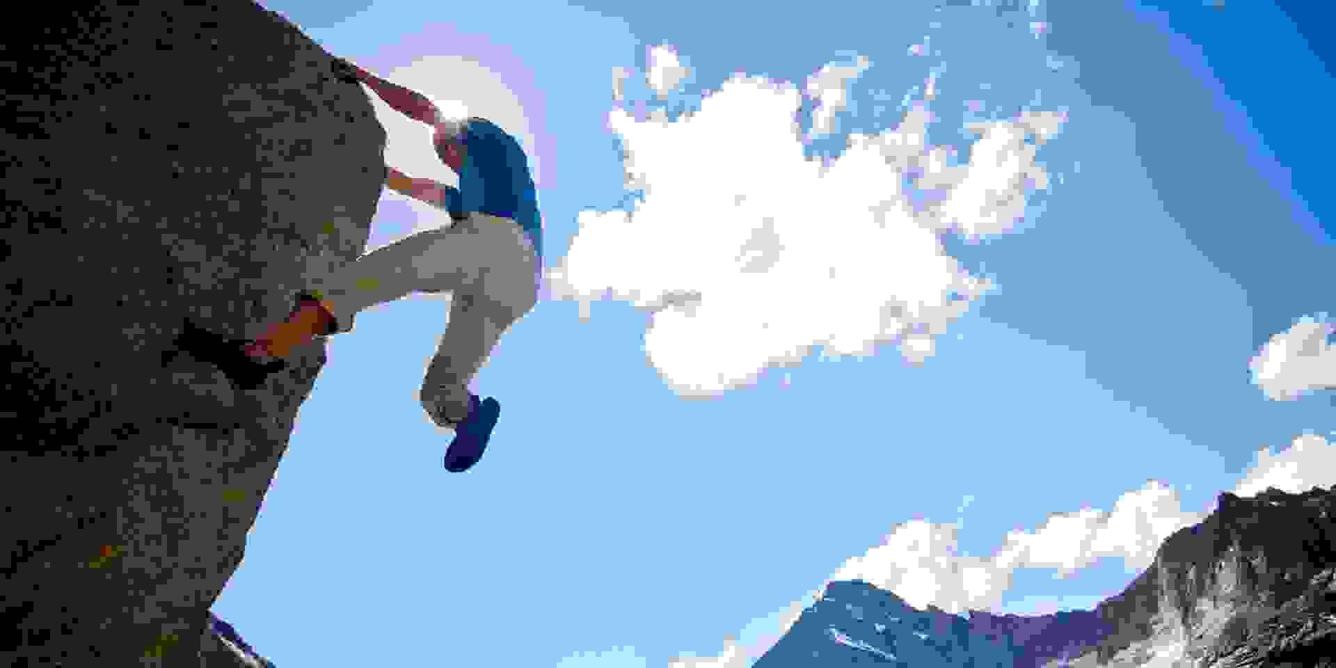 Ein mann bouldert vor einem Bergpanorama im Freien