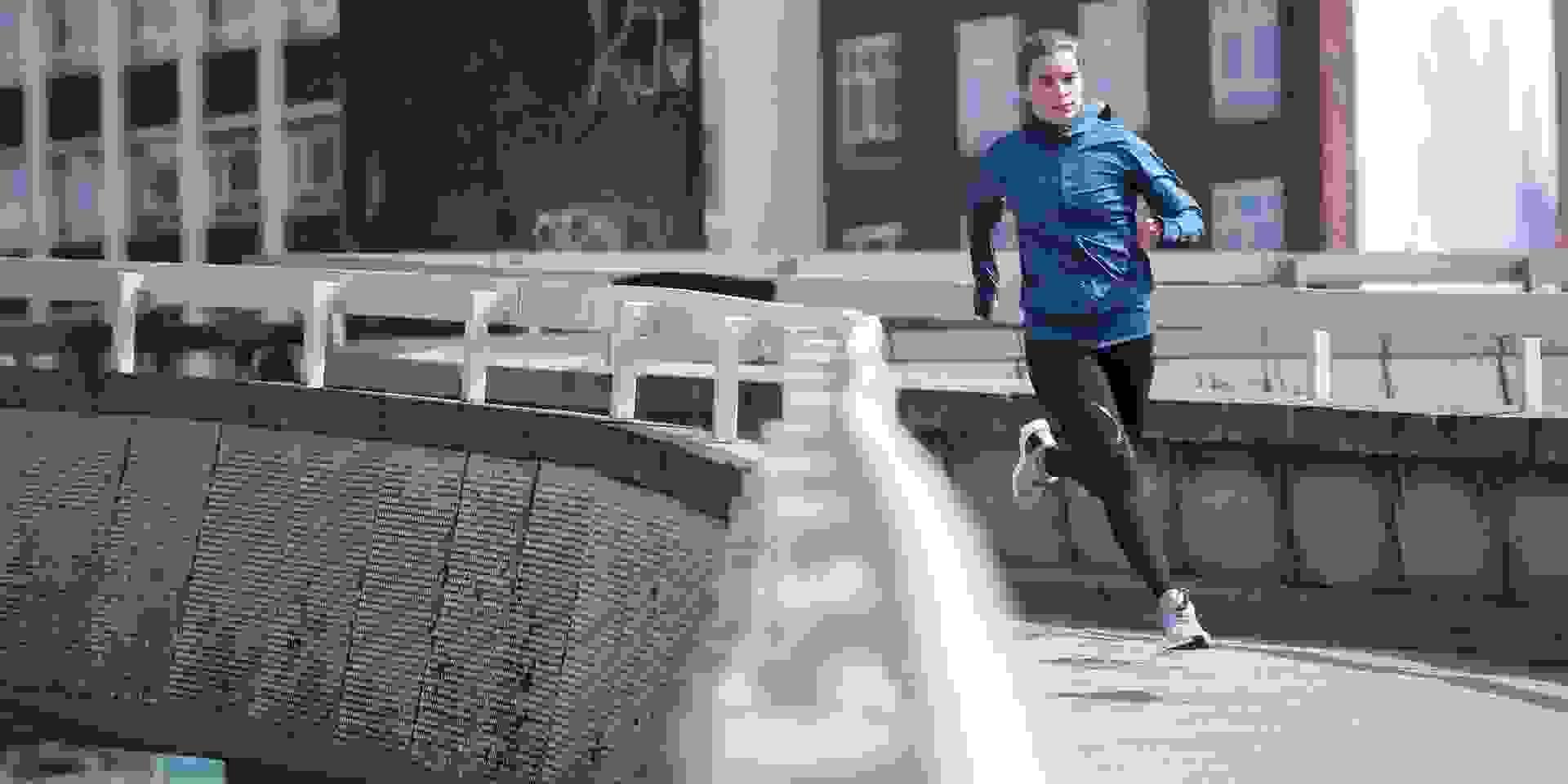 Eine Frau trainiert bei einem Lauf bei kaltem Herbstwetter in der Stadt