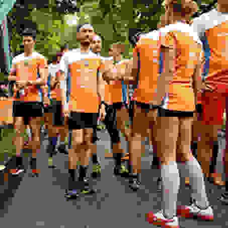 Diverse Läufer stehen vor dem Start beim Hamburg Stadtlauf in einer Gruppe zusammen.