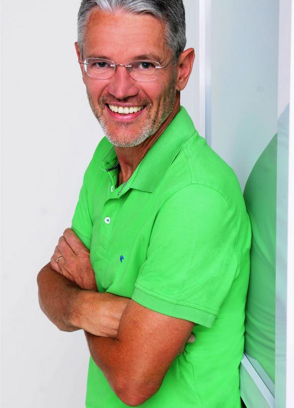Portrait Aufnahme von Harry Hüttmann. Er lehnt mit verschränkten Armen an einer weißen Wand und trägt ein grünes Poloshirt.
