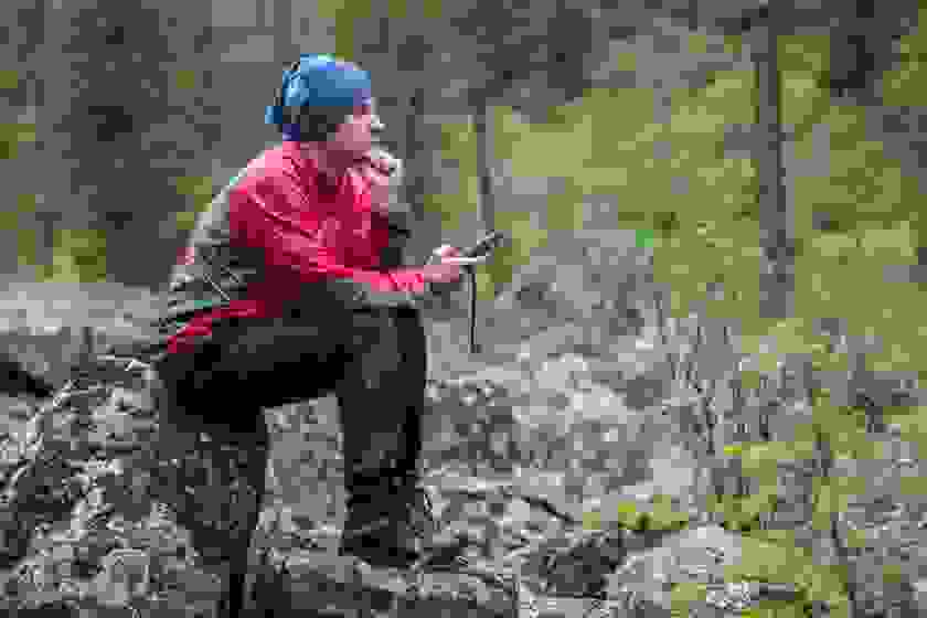 Ein Mann sitzt im Wald auf einem großen Stein und hält sein Navigationsgerät in der Hand.