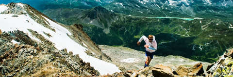 Ein Mann läuft auf einem steinigen Gebirgsweg einen Trail.