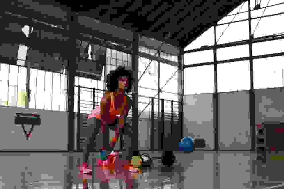 Eine Frau trainiert mit Kettlebells in einer Sporthalle.
