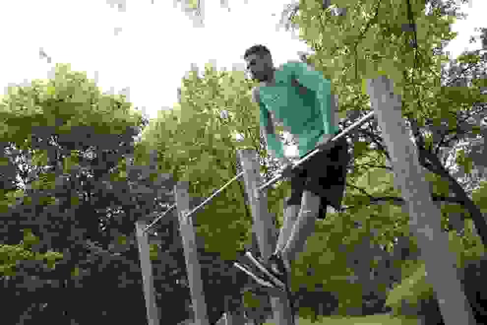 Ein Mann trainiert an einem Klettergerüst in einem Park.