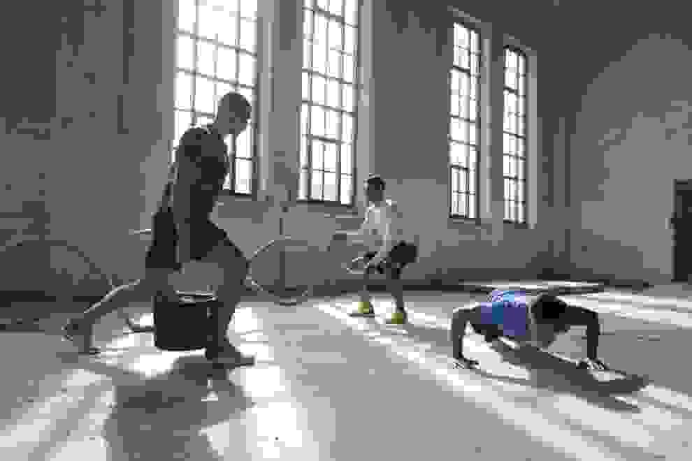 3 Männer betreiben Functional Training in einer Lagerhalle.