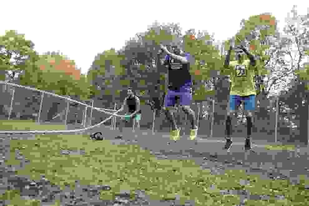 Drei Männer trainieren mit ihrem Körpergewicht auf einem Rasenplatz.