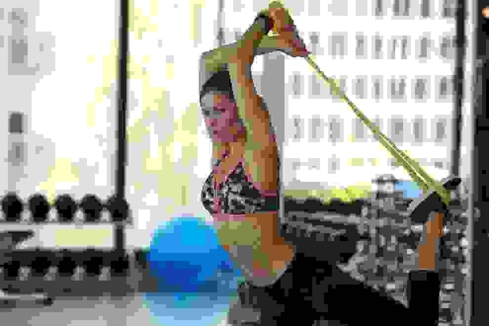 Eine Frau trainiert im Fitnessstudio mit einem Gymnastikband.