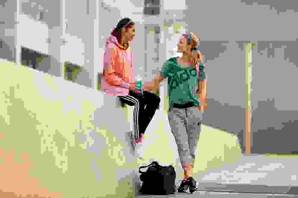 2 Frauen unterhalten sich auf der Straße. Beide tragen Trainingsoutfits.