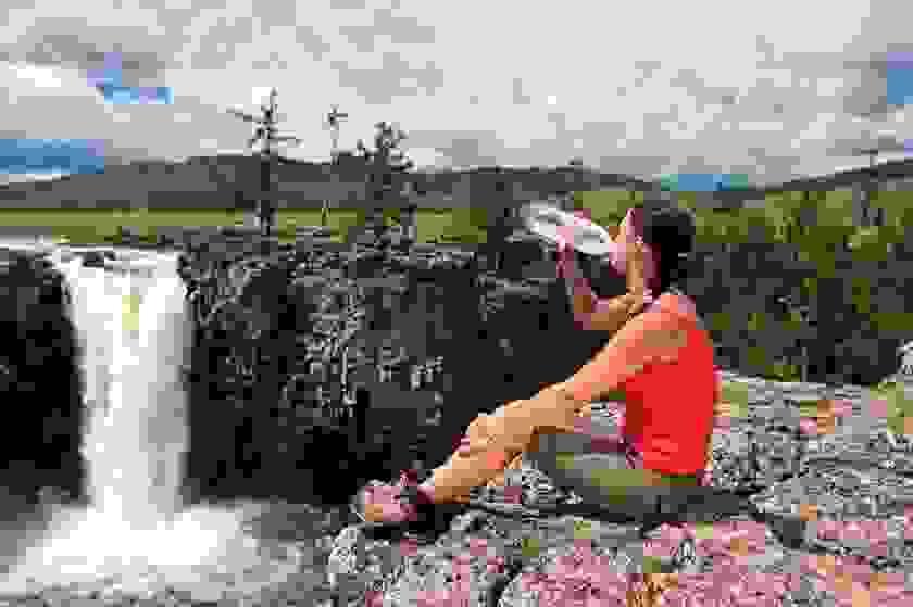 Eine Frau sitzt auf einem Berg und trinkt aus einer Wasserflasche.