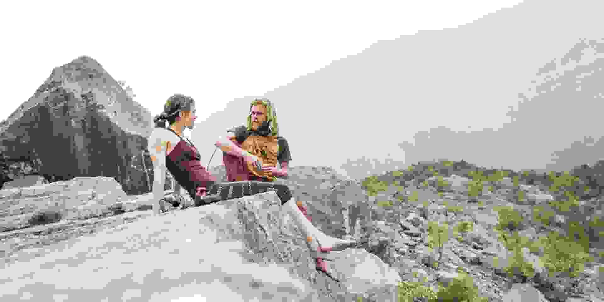 Ein Mann und eine Frau sitzen auf einem Felsen und unterhalten sich.