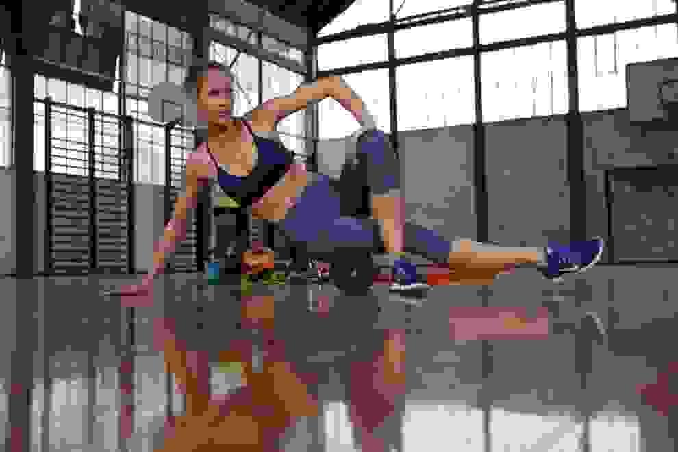 Eine Frau trainiert in einer Sporthalle mit eine Faszienrolle.