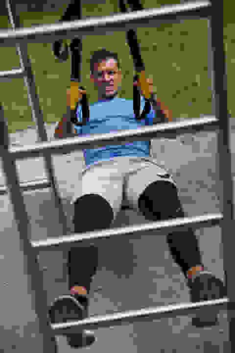 Ein Mann trainiert mit einem Schlingentrainer mit seinem eigenen Körpergewicht.