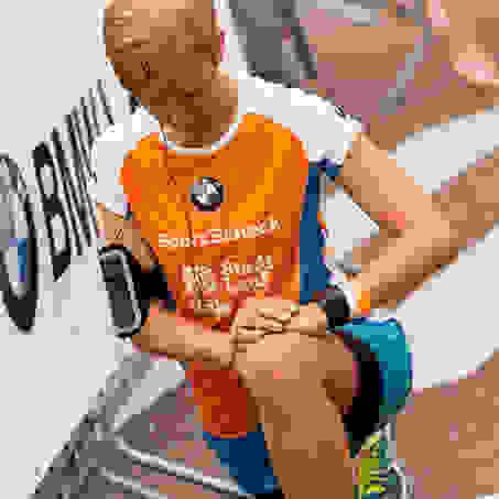 Eine Frau dehnt vor dem Start des Stadtlaufs in Köln ihre Beinmuskulatur.