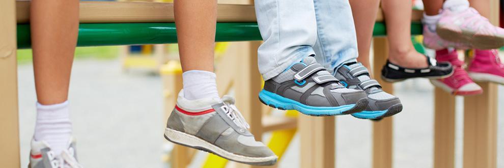 Kinder sitzen auf einer erhöhten Bank. Die Füße baumeln in unterschiedlichen Kinderschuhen in der Luft.
