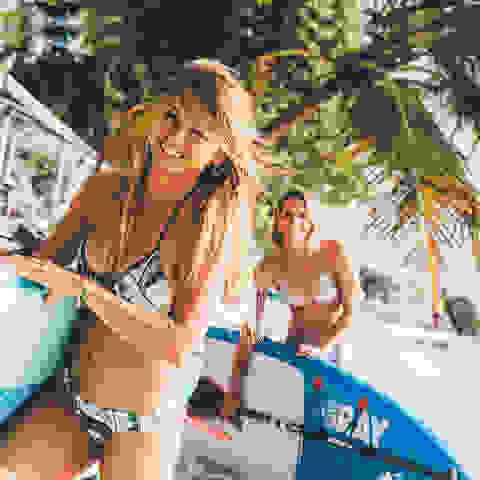 Zwei Frauen mit Surfbrett.