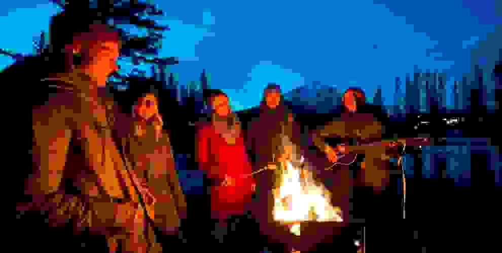 Eine Gruppe von Leuten steht am Abend um ein Lagerfeuer herum. Eine Frau spielt dazu Gitarre.