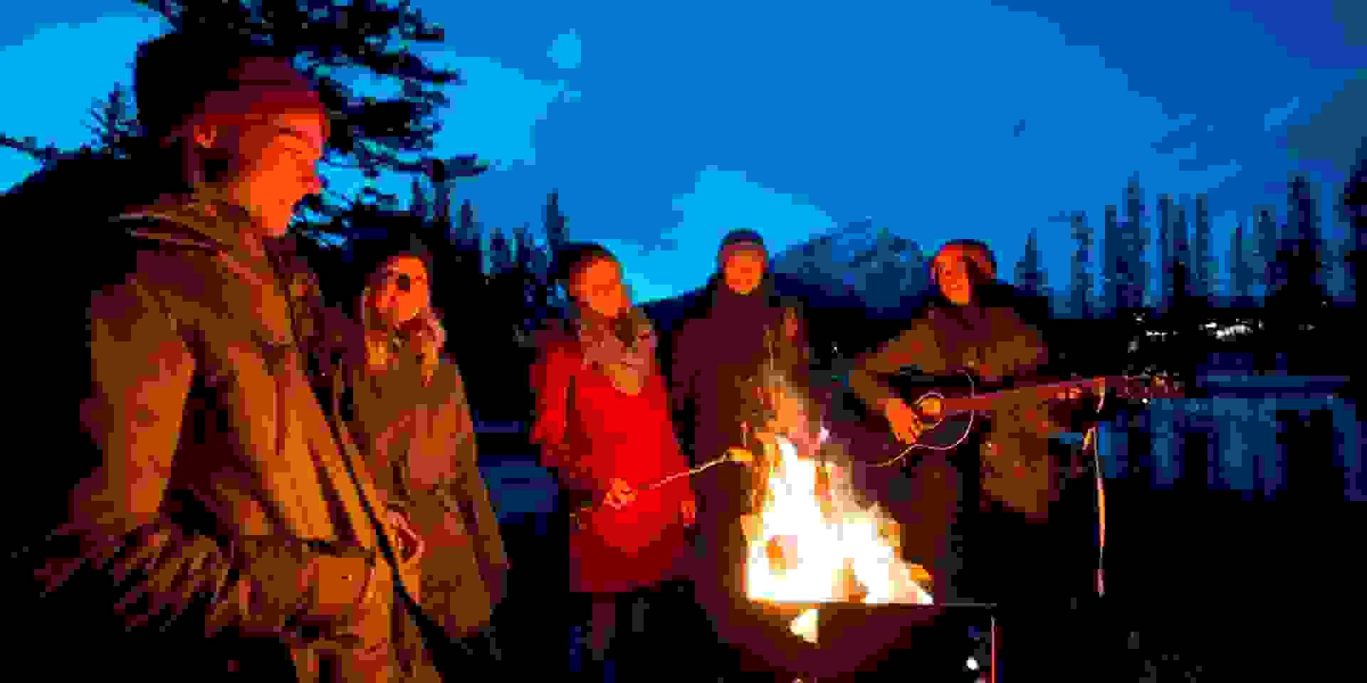 Eine Gruppe Wanderer steht am Lagerfeuer und wärmt sich auf.