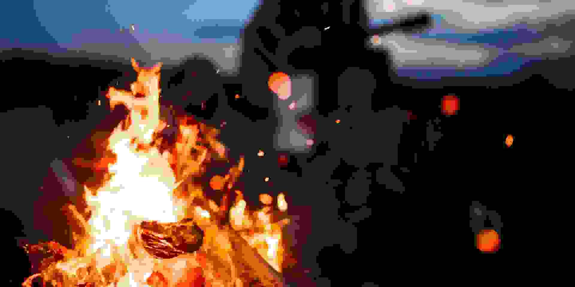 Ein Lagerfeuer brennt in der Nacht und wärmt Wanderer.