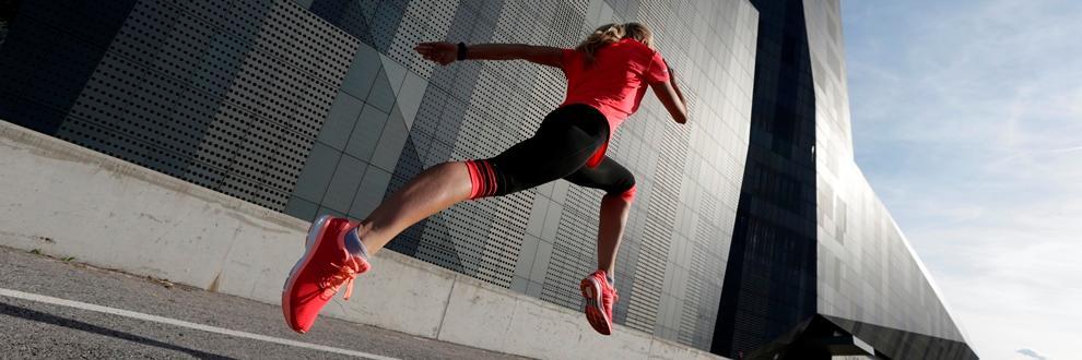 Eine Frau läuft einen 10 km Lauf. Sie trägt eine schwarze Lauftights und ein rotes Laufshirt.