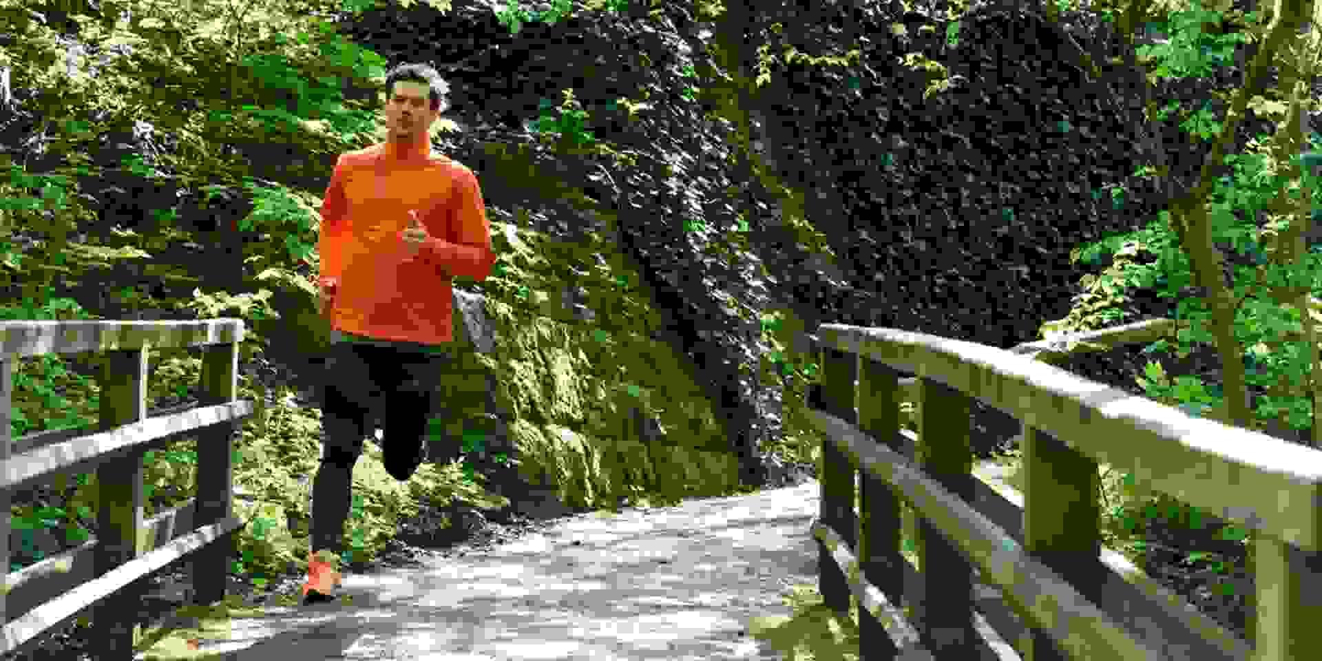 Ein Läufer bereitet sich auf den Halbmarathon vor. Er läuft durch einen Wald und überquert eine Holzbrücke.
