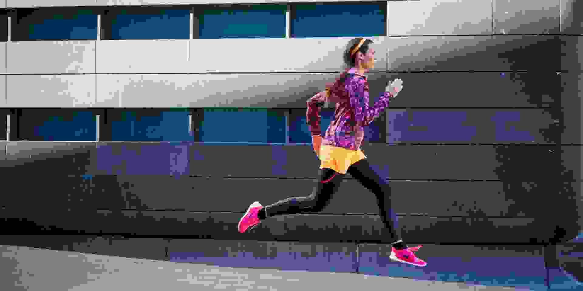 Eine Frau traininert für einen Halbmarathon. Sie läuft eine Straße entlang.