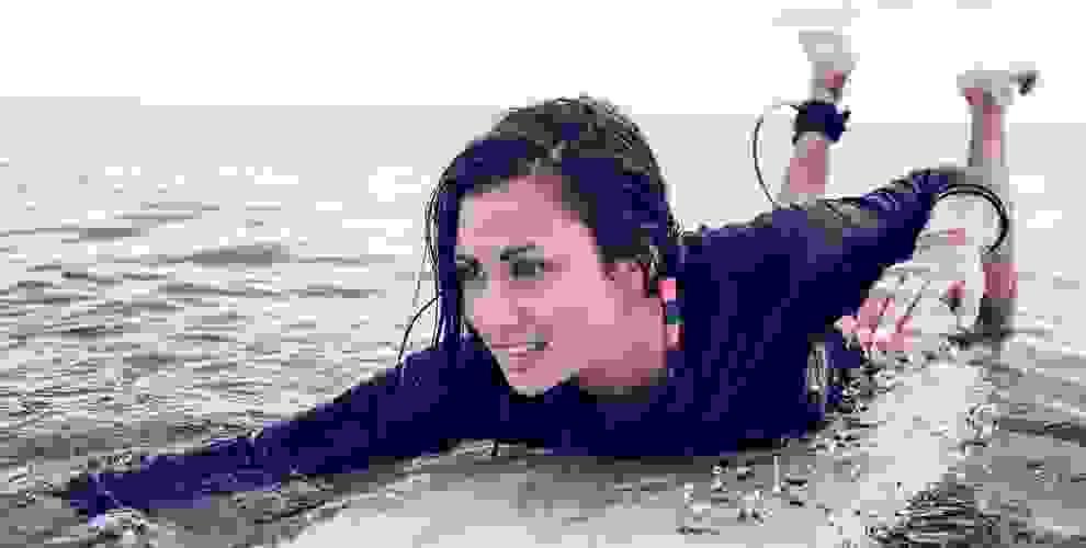Eine Frau liegt im Wasser auf ihrem Surfbrett und paddelt mit den Armen. Sie trägt einen Surfanzug aus Lycra.