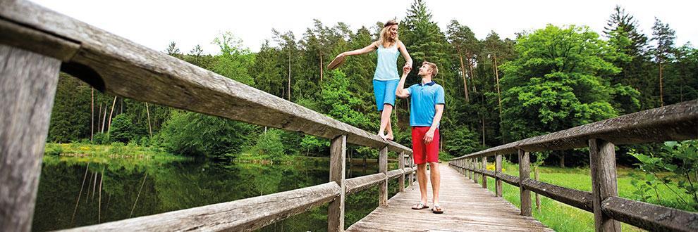 Ein Mann und eine Frau gehen über eine Holzbrücke. Die Frau balanciert dabei auf dem Geländer und der Mann hält sie an der Hand um sie zu stützen. Beide tragen Kleidung von Maier Sports.