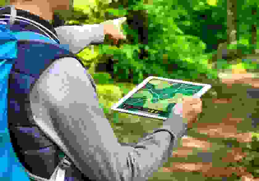 Ein Mann hält ein Tablet in der Hand. Darauf zu sehen ist eine geöffnete Navigationsapp, die den Weg zum nächsten Cache anzeigt.